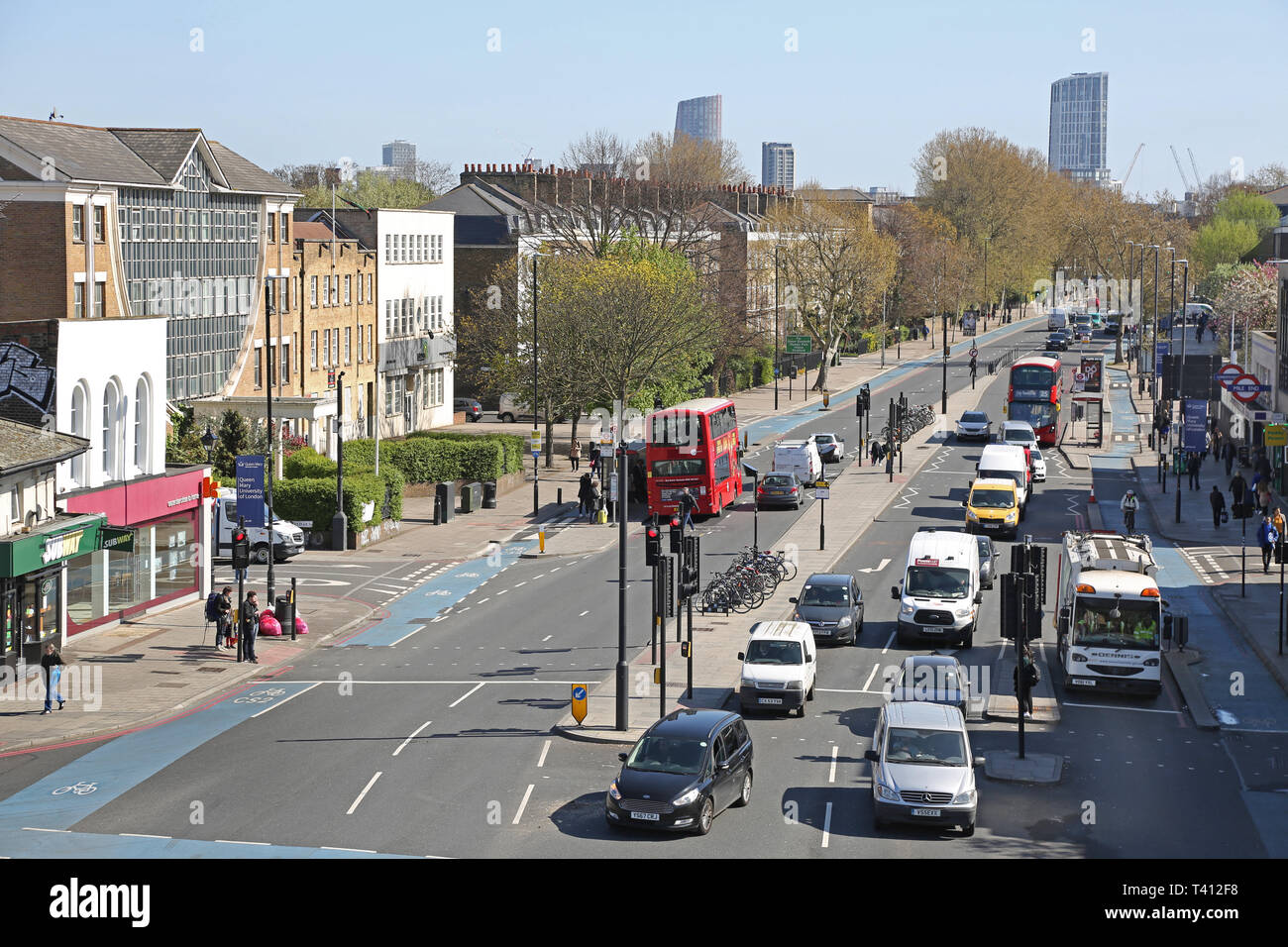 Fully integrated cycle routes on Mile End Road / Bow Road in London's East End. View east towards Bow. Shows cycle supehighway, bus lanes, bus stops. - Stock Image