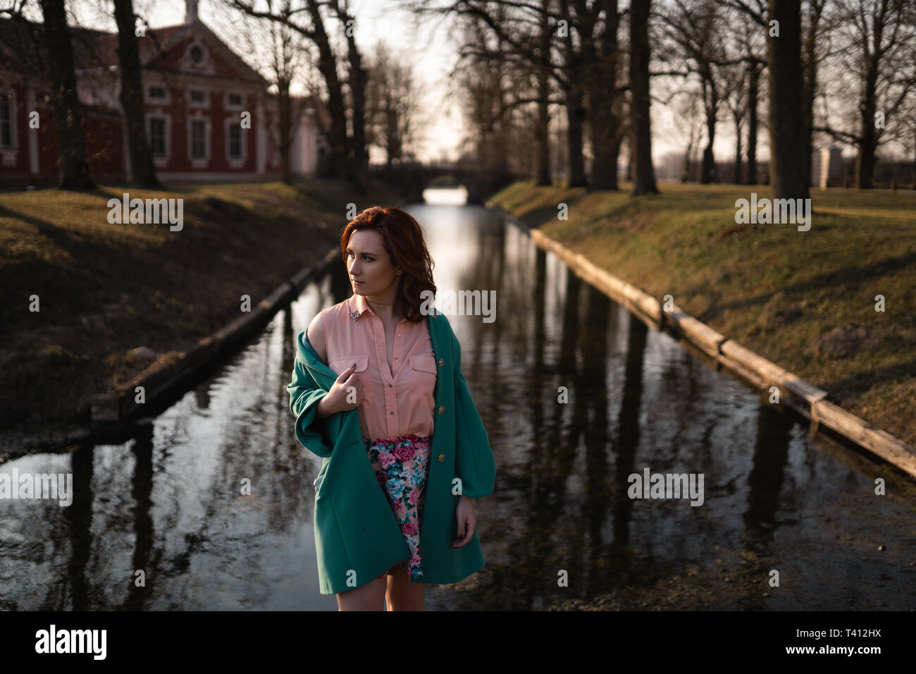 Beautiful young woman relaxing near a canal river in a park near the palace in Rundale, Latvia, 2019 Stock Photo