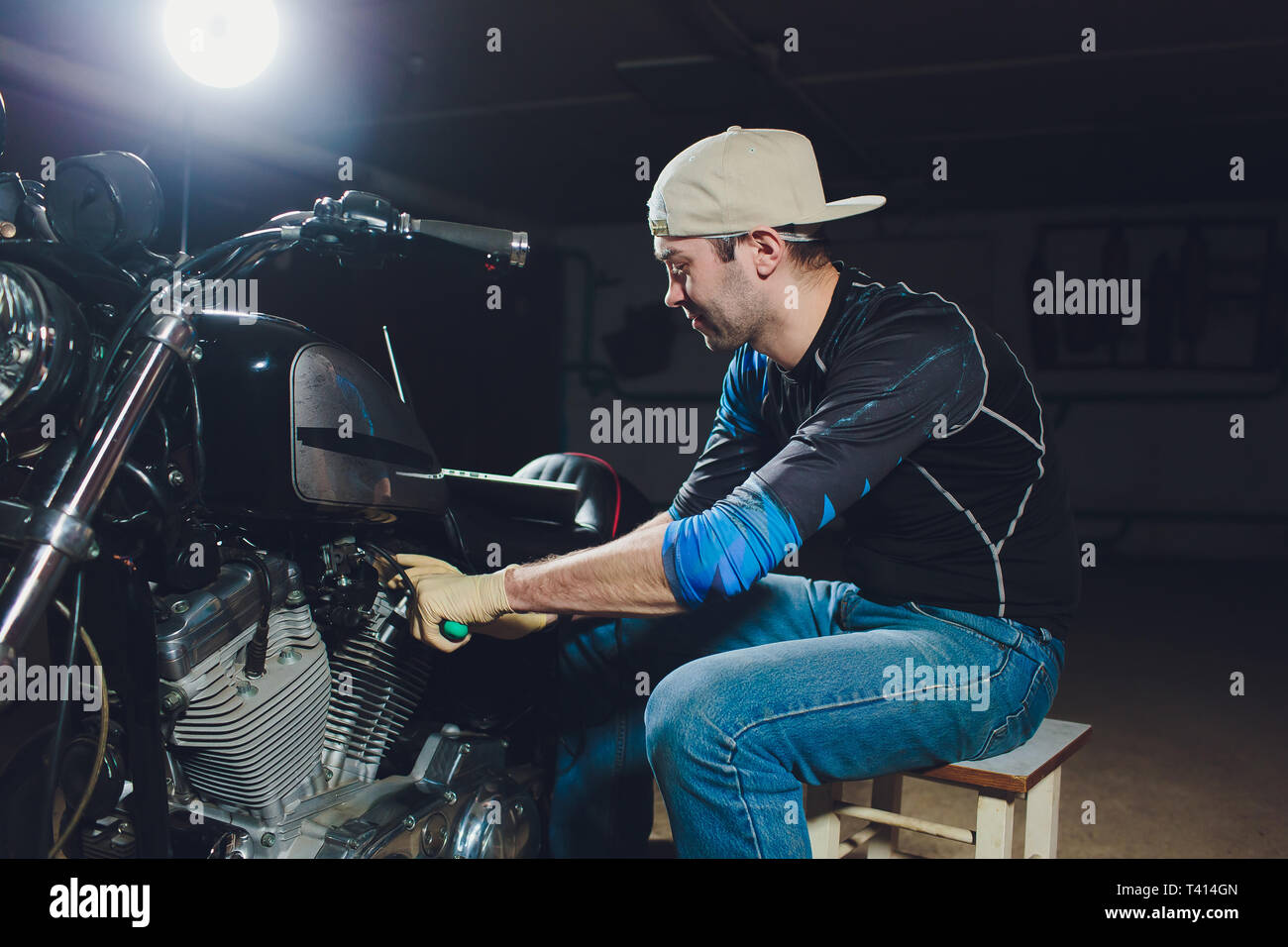 motorcycle mechanic repairing engine under supervisors guidance. video camera, laptop to view the inside of the engine to check soot. - Stock Image