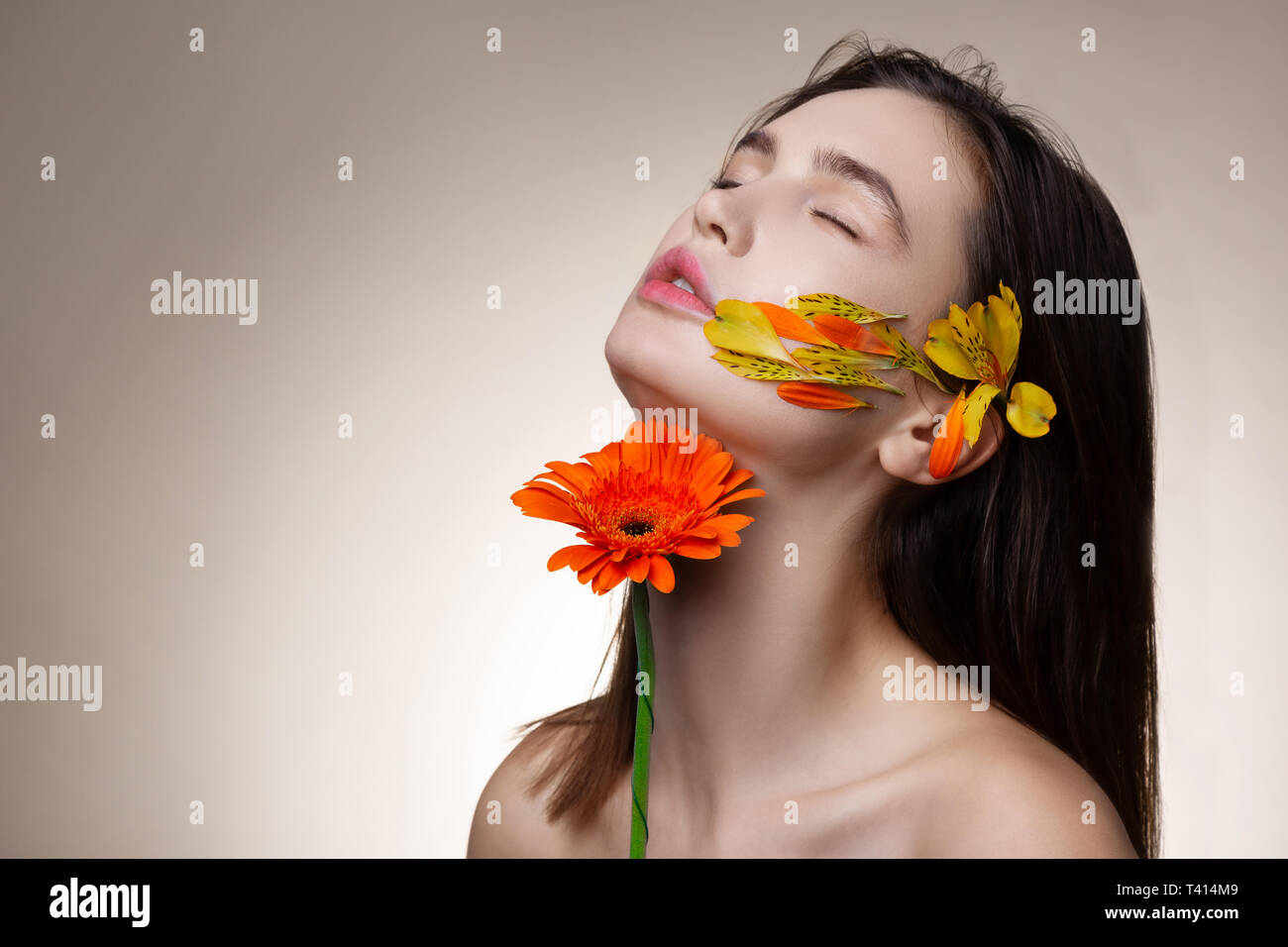 Model getting true satisfaction while posing with flowers - Stock Image