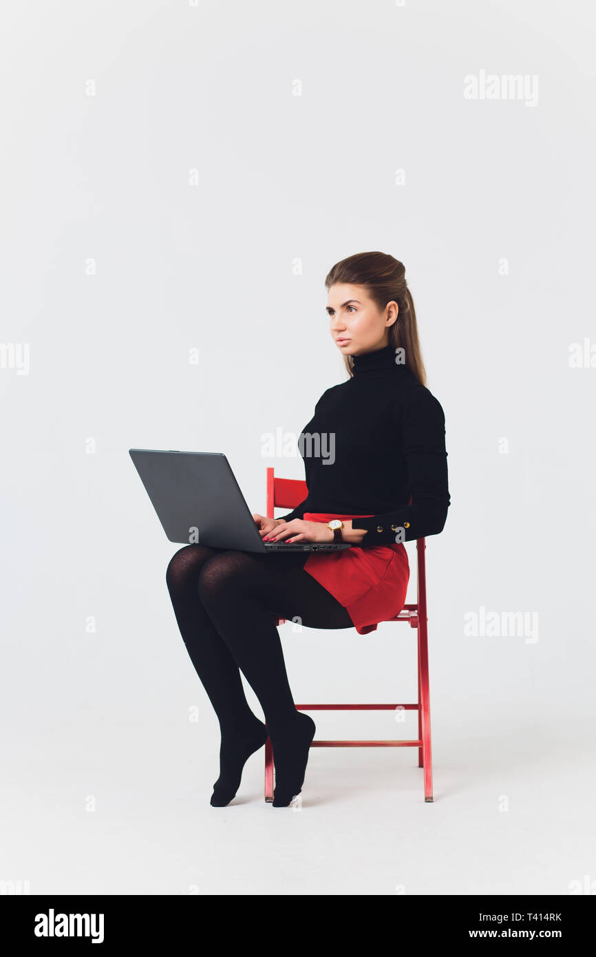 Photo of beautiful woman 20s smiling and using computer with legs crossed isolated over white background. - Stock Image