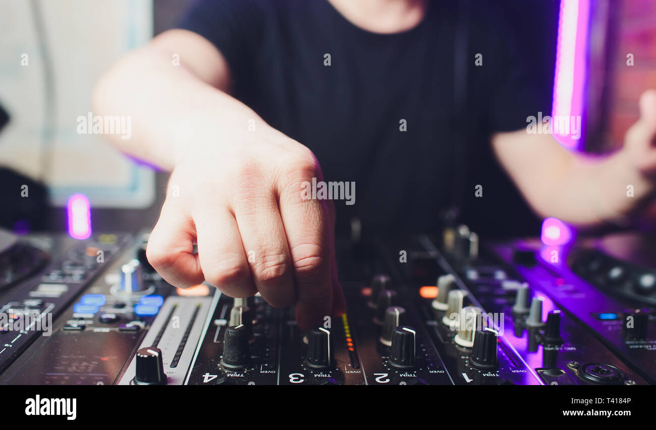 Close up view of the hands of male disc jockey mixing music on his deck with his hands poised over the vinyl record on the turntable and the control - Stock Image