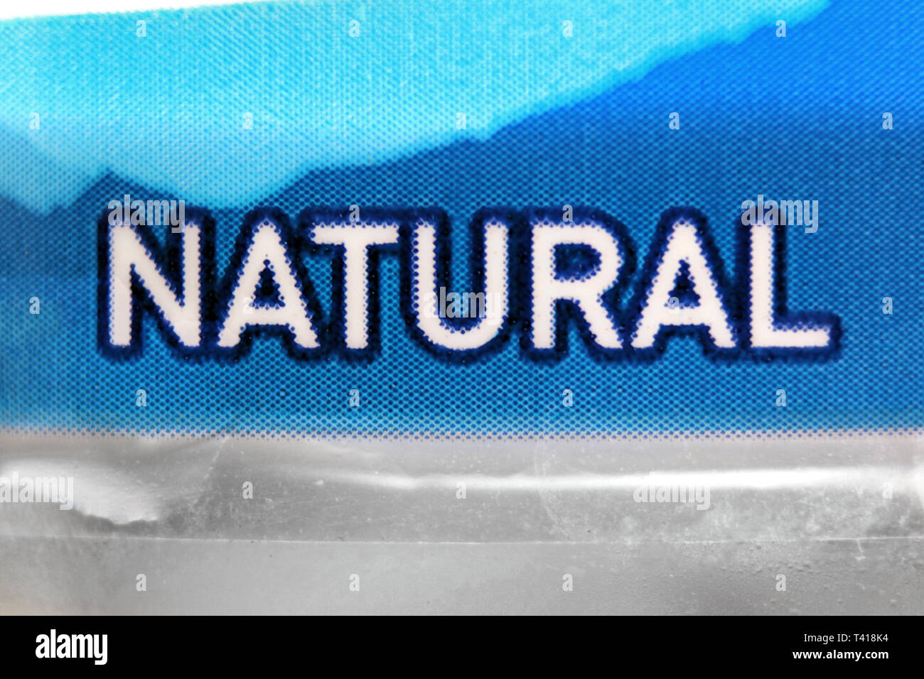 Natural printed on label in plastic disposable water bottle, close-up - Stock Image