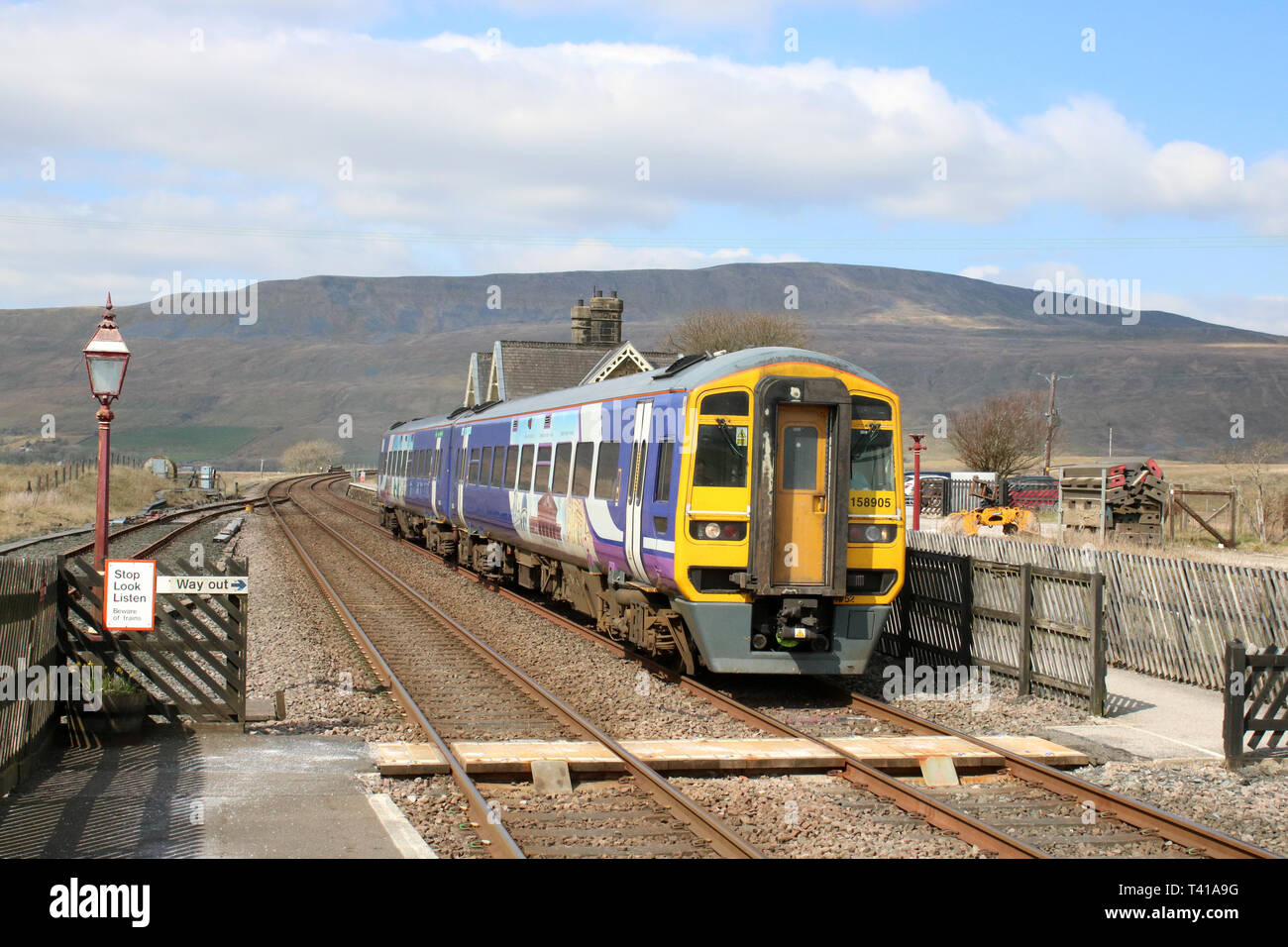 Class 158 express sprinter dmu passenger train in Northern livery leaving Ribblehead station on the Settle to Carlisle railway line 12th April 2019. - Stock Image