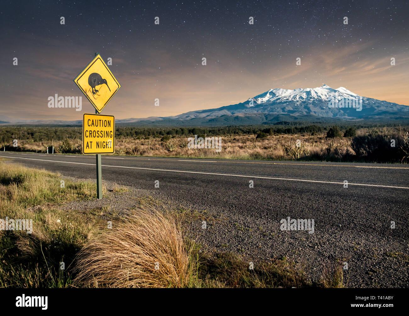 Kiwi crossing sign at night next to snowy Mount Ruapehu in New Zealand's Tongariro national park. - Stock Image