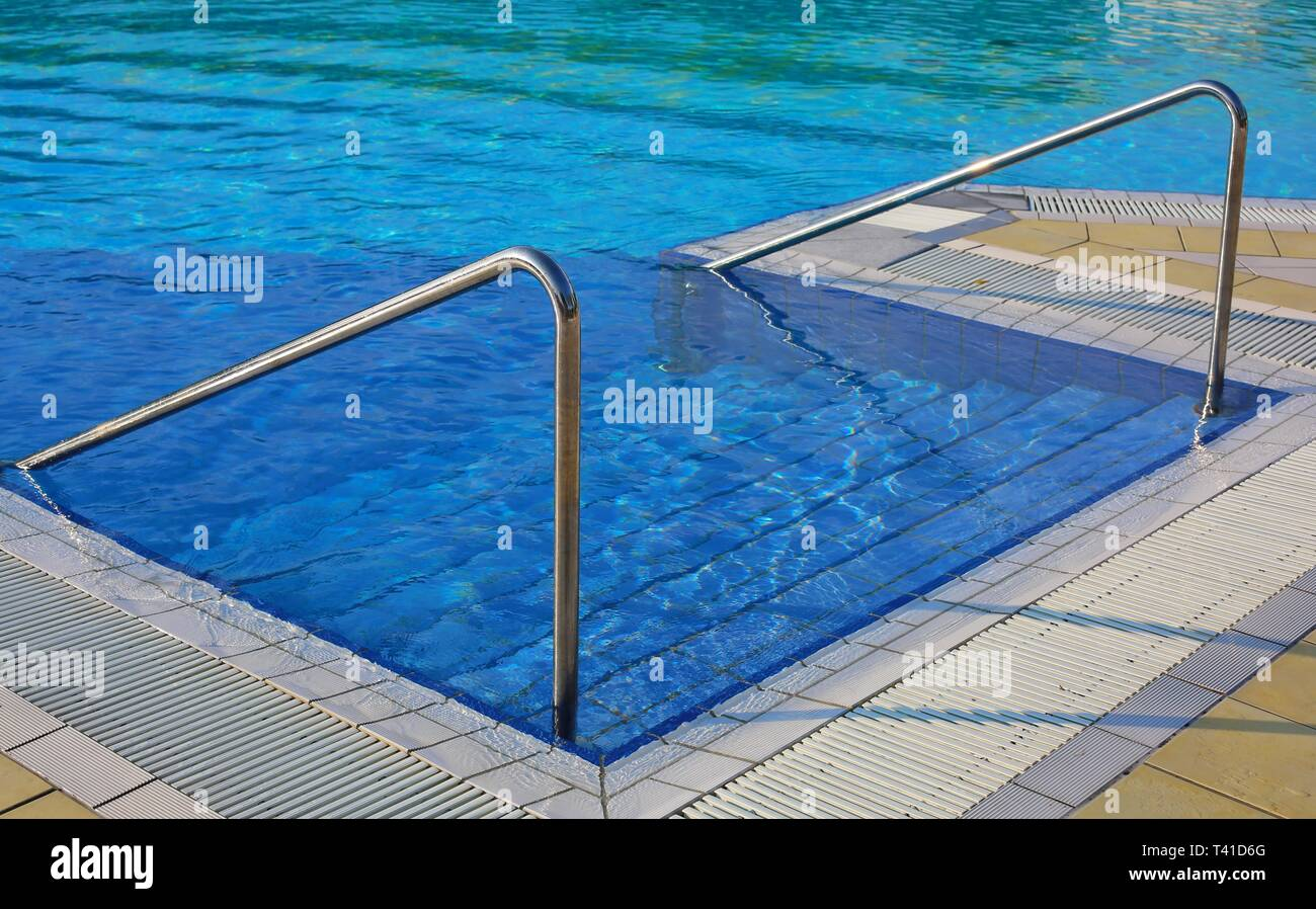 Swimming pool with ladder and steel handrail in the spa ...
