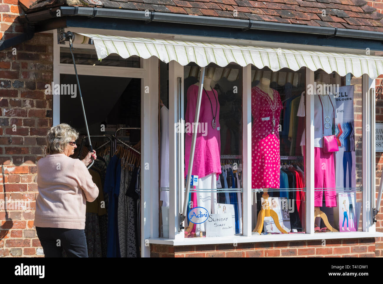 Woman extending awning outside a small local independent clothing store in the UK. - Stock Image