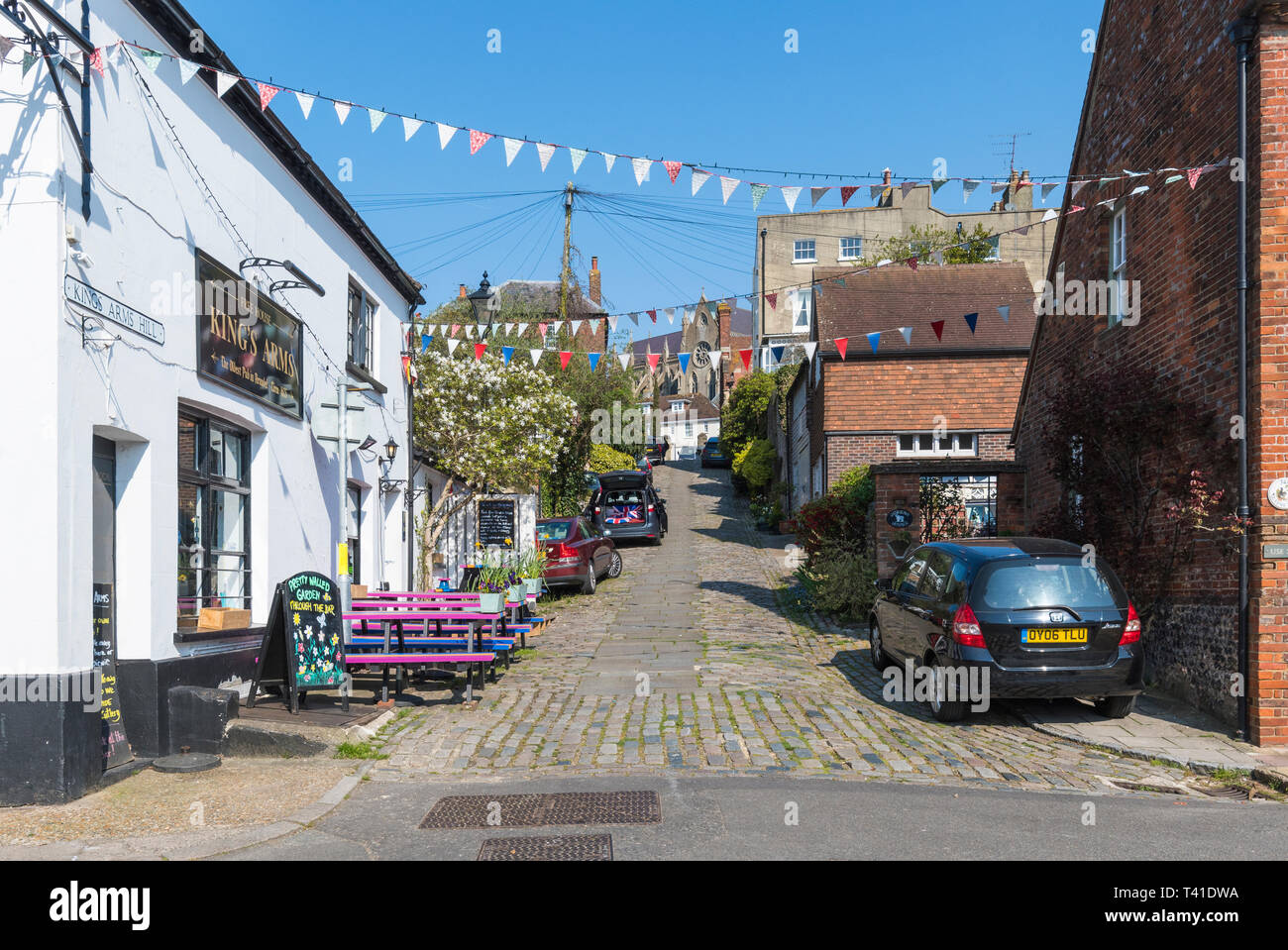 Cars parked on Kings Arms Hill, a steep cobbled road in Arundel, West Sussex, England, UK. - Stock Image