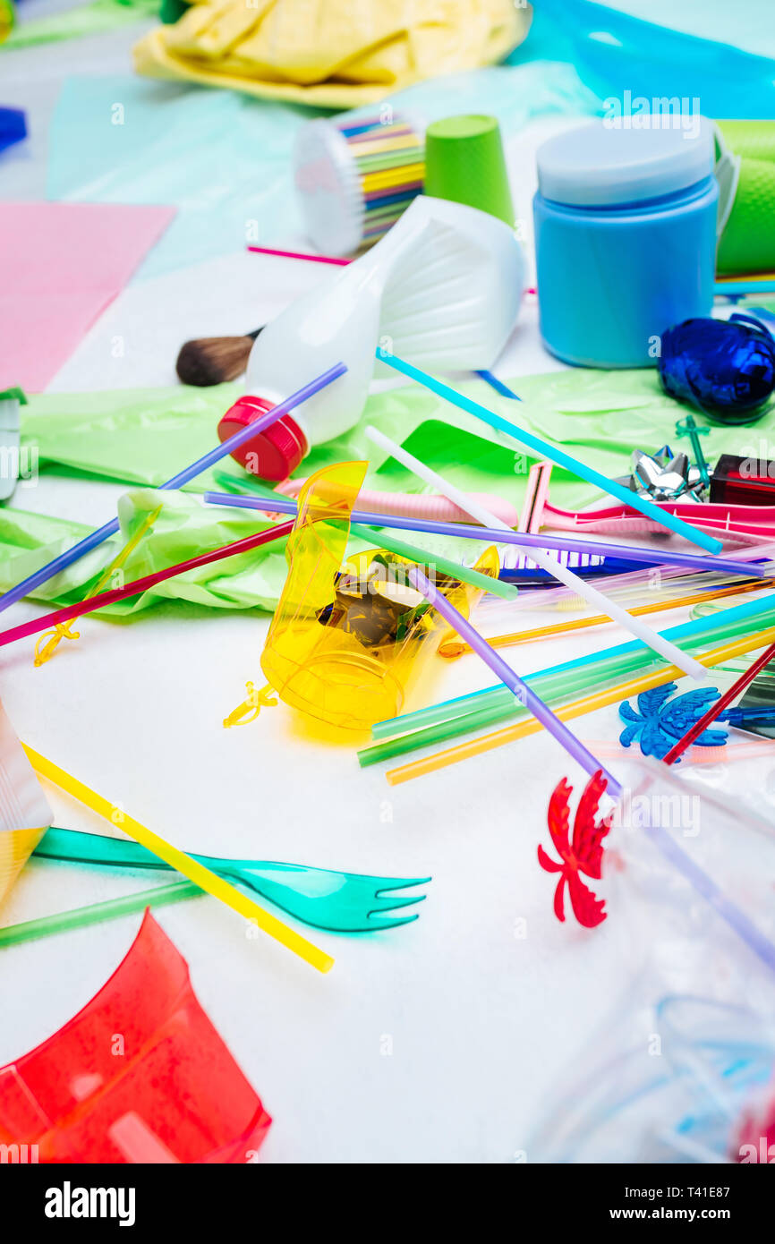 Cutlery and straws. Close up of plastic cutlery and straws lying near other trash harming and polluting nature - Stock Image