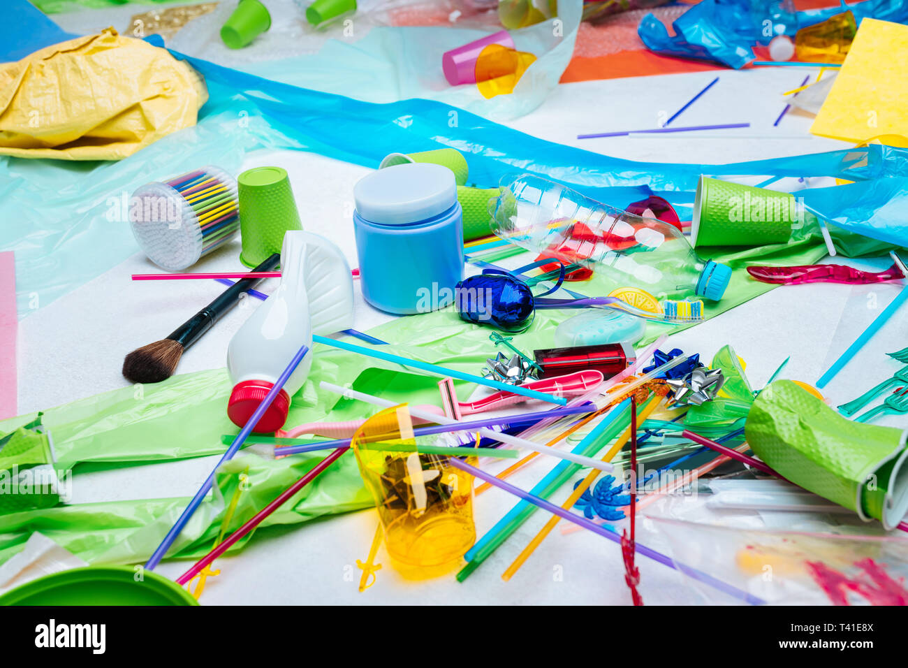 Polluting nature. Different colorful plastic items harming and polluting nature lying on the floor - Stock Image