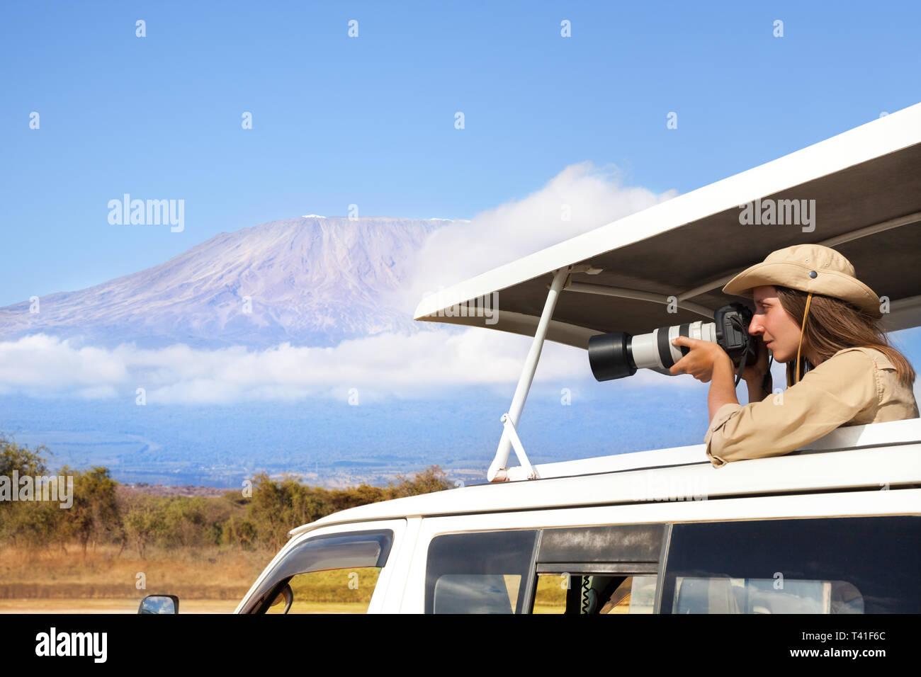 Woman taking shoot of African savannah with Kilimanjaro mount background during safari game drive - Stock Image