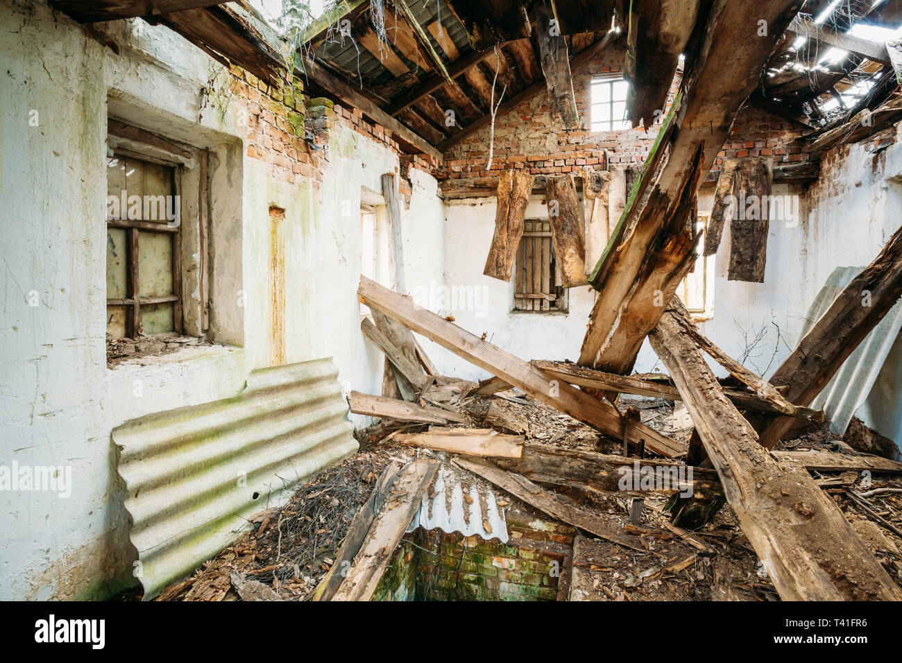 Belarus. Interior Of Ruined Abandoned Private Country House With Caved Roof In Evacuation Zone After Chernobyl Disaster. Terrible Consequences Of Nucl - Stock Image
