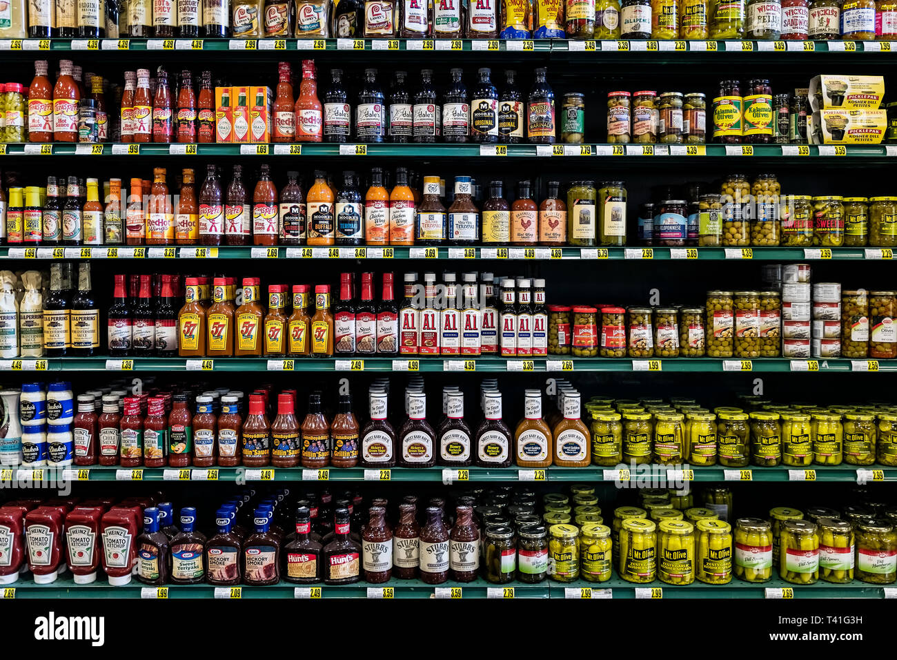 Condiment brands displayed on the shelves of a grocery store. Stock Photo