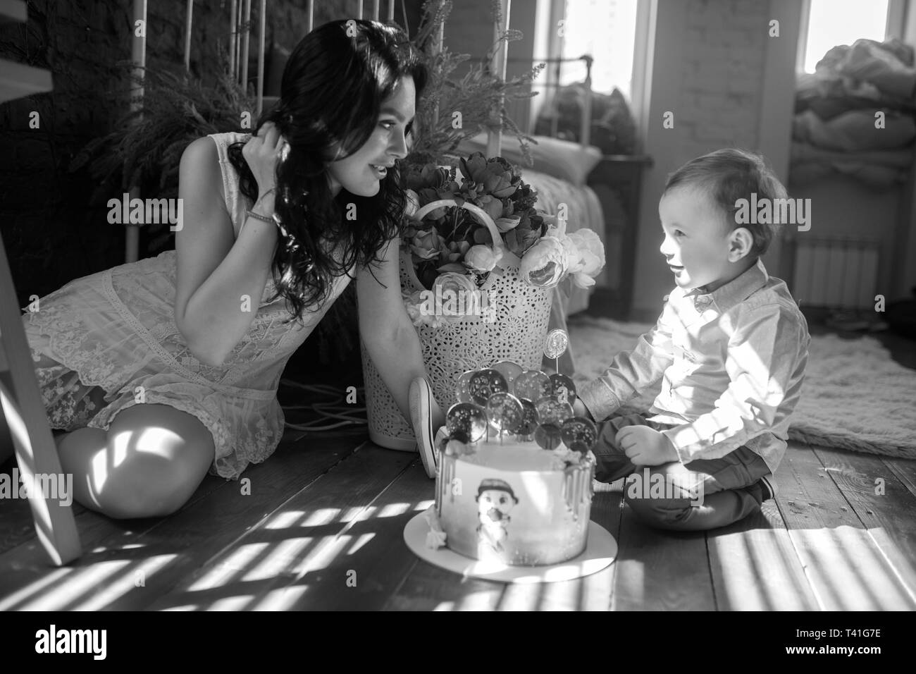 Toddler boy sits on floor with his mother near birthday cake on background of flowers. Black and white image. - Stock Image