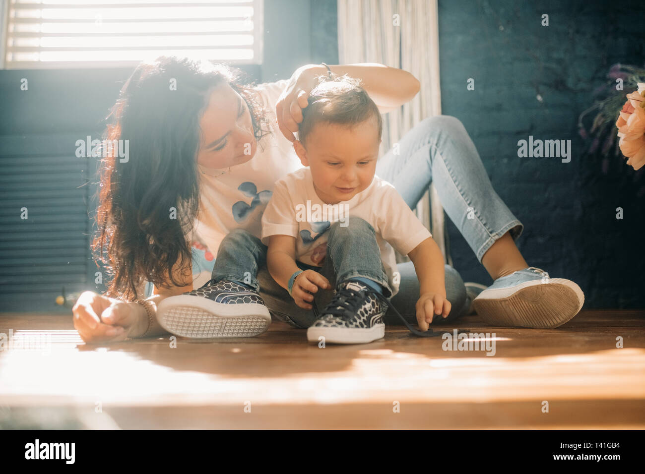 Toddler boy ties the shoelaces on his sneakers next to his mother. - Stock Image