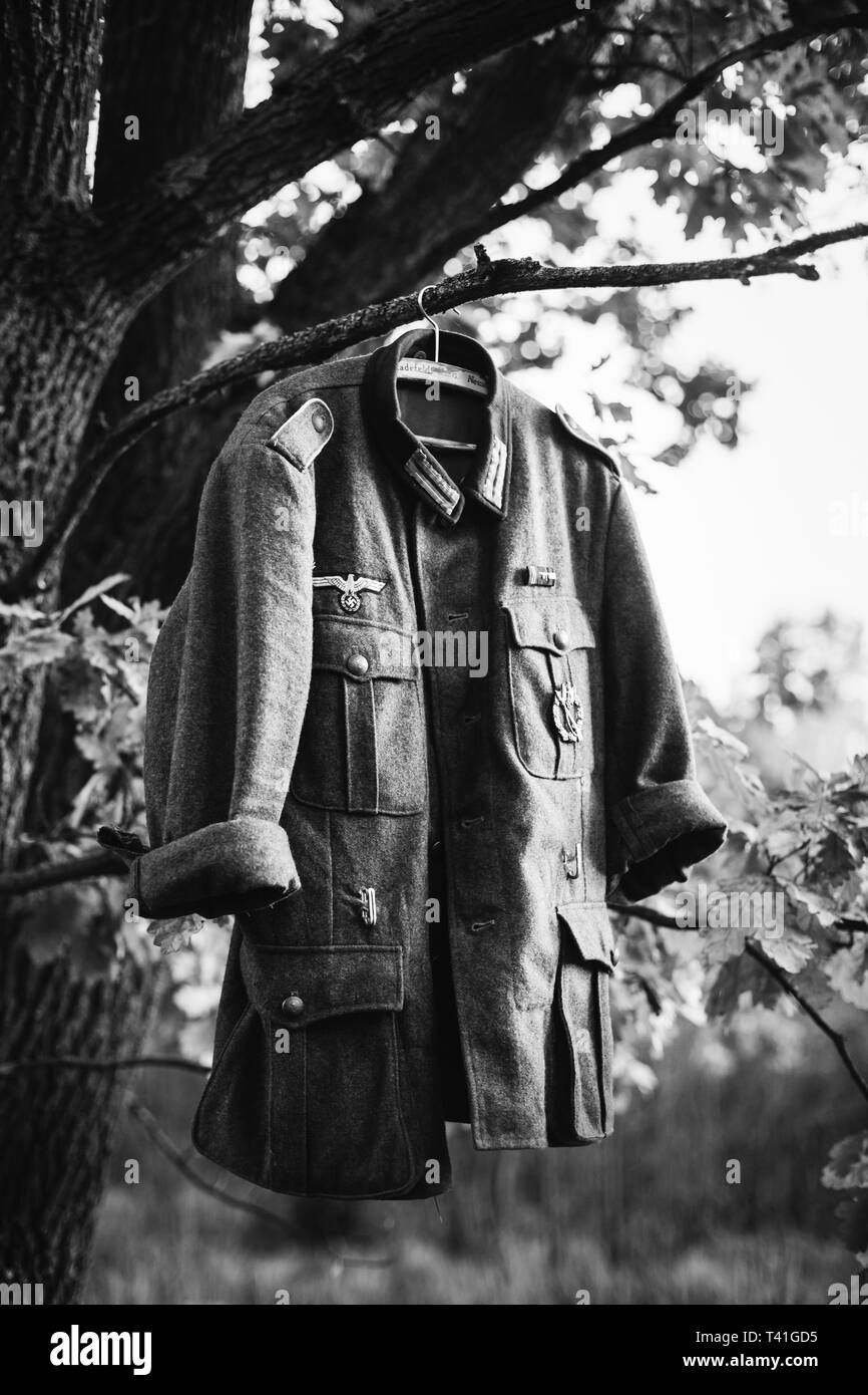 Single Coat Or Tunic Of World War II German Wehrmacht Infantry Soldier Hanging On A Hanger On Wood Outdoors In Camp. WWII WW2 Times. Uniform Of German - Stock Image