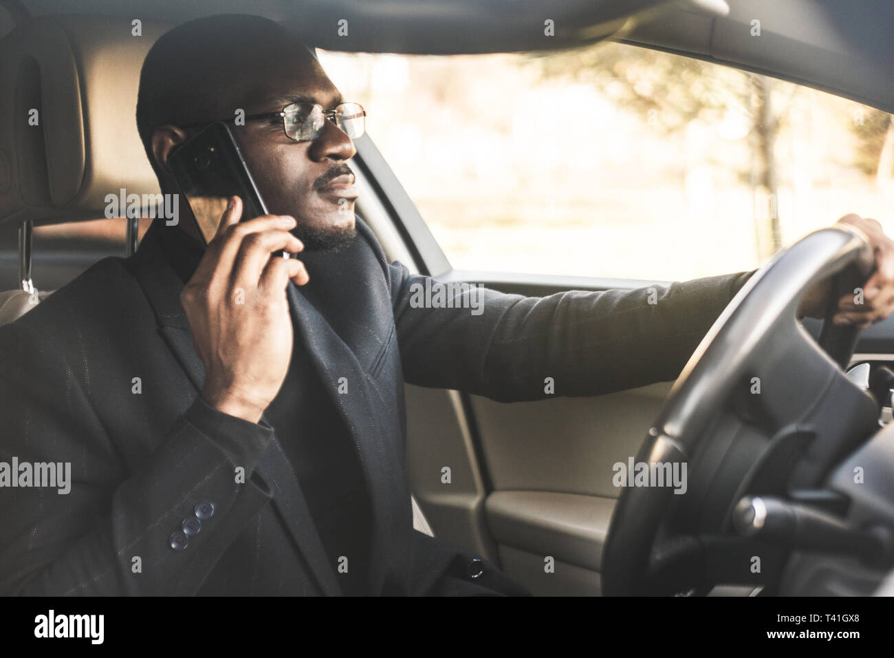 A businessman driving a expensive car holds a mobile phone in his hand. Hasty life - Stock Image
