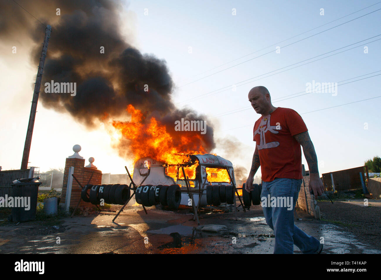 A man walks past a burning barricade during the eviction of Dale Farm. Basildon. Essex. 19 October 2011. - Stock Image