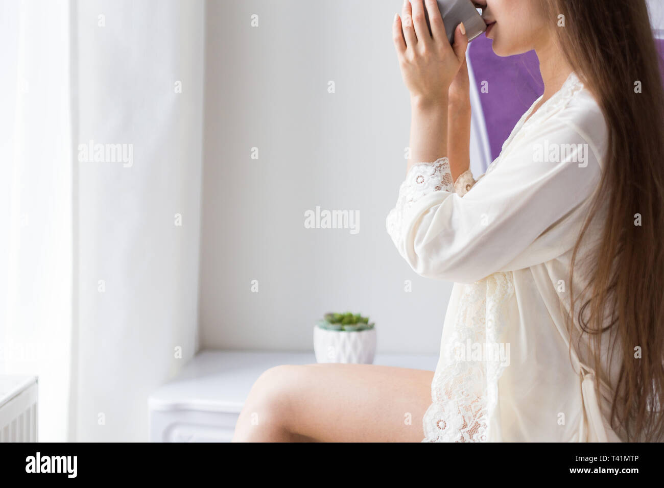Attractive young girl in nightwear sits on the edge of the bed by the window and drinks coffee from a mug. - Stock Image