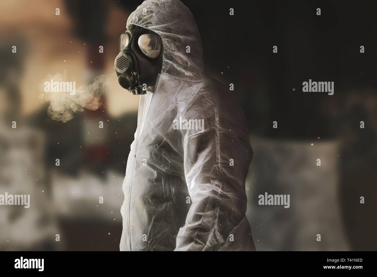 survivor with white overall and gas mask in front of blurred incineration plant and apocalyptic environment - Stock Image