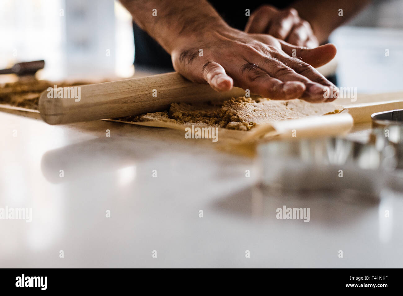 Dad rolling cookie dough for baking - Stock Image