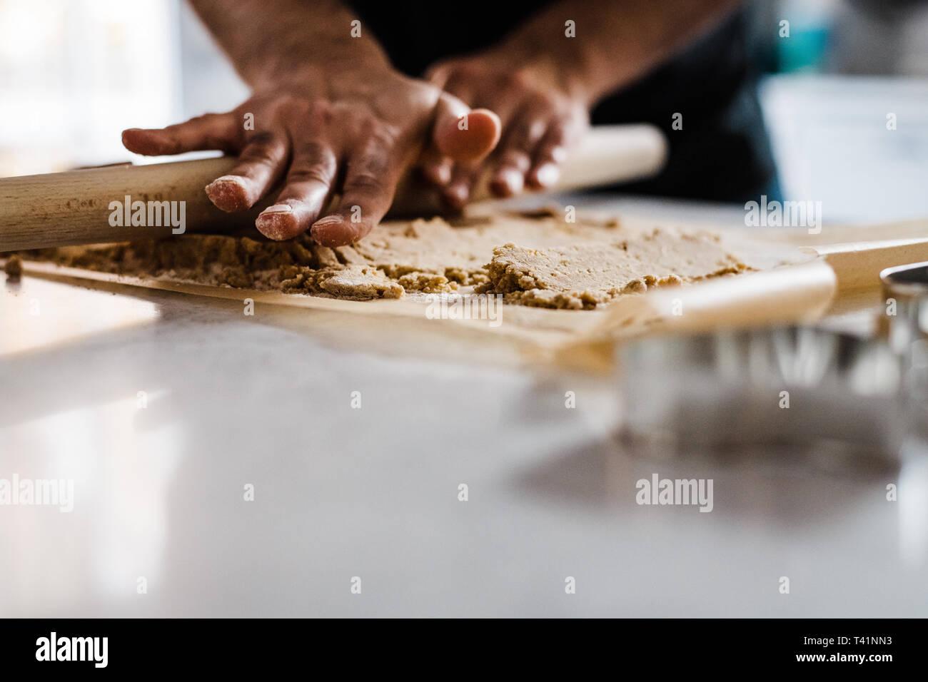 Man's hands rolling dough - Stock Image