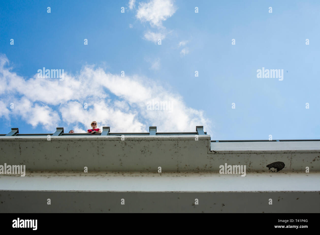 a view from below of blue sky and two people peering over a bridge - Stock Image