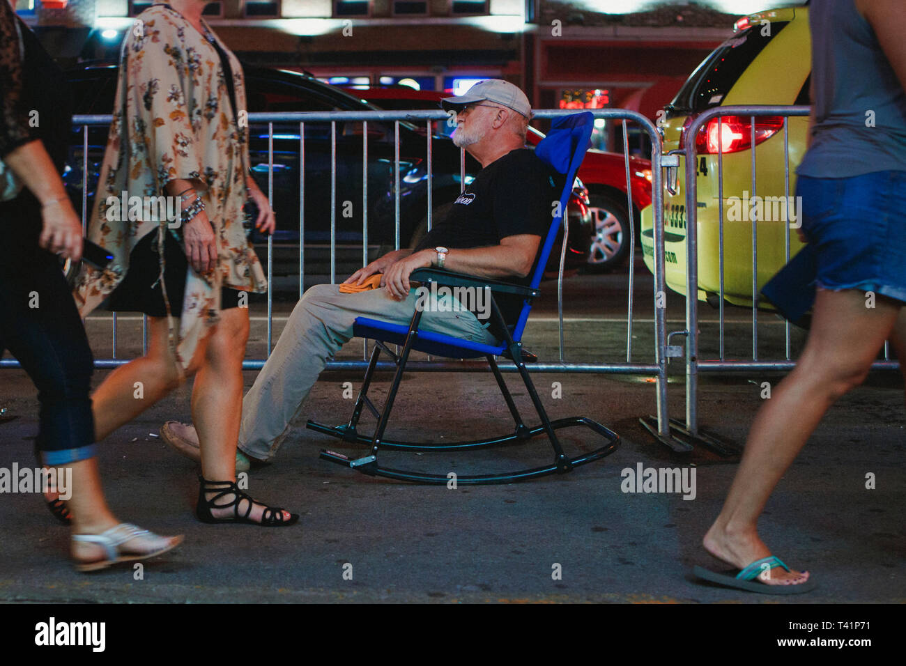 a man sits in a rocker in the middle of a crowded sidewalk at night Stock Photo