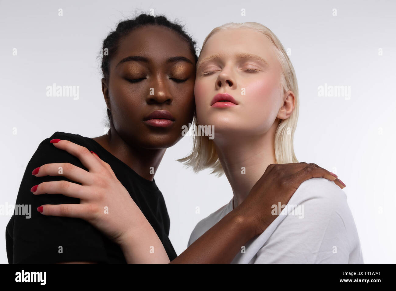Diversity and anti-racism. Two good-looking young models posing for article about diversity and anti-racism - Stock Image