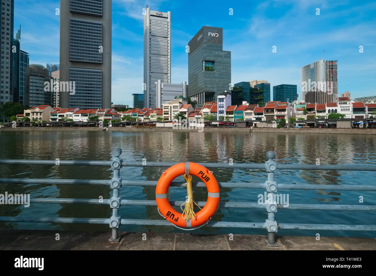 A lifesaver attached by the Public Utilities Board (PUB) to the railing along the Singapore River, at Boat Quay, Singapore; b/g: financial district - Stock Image