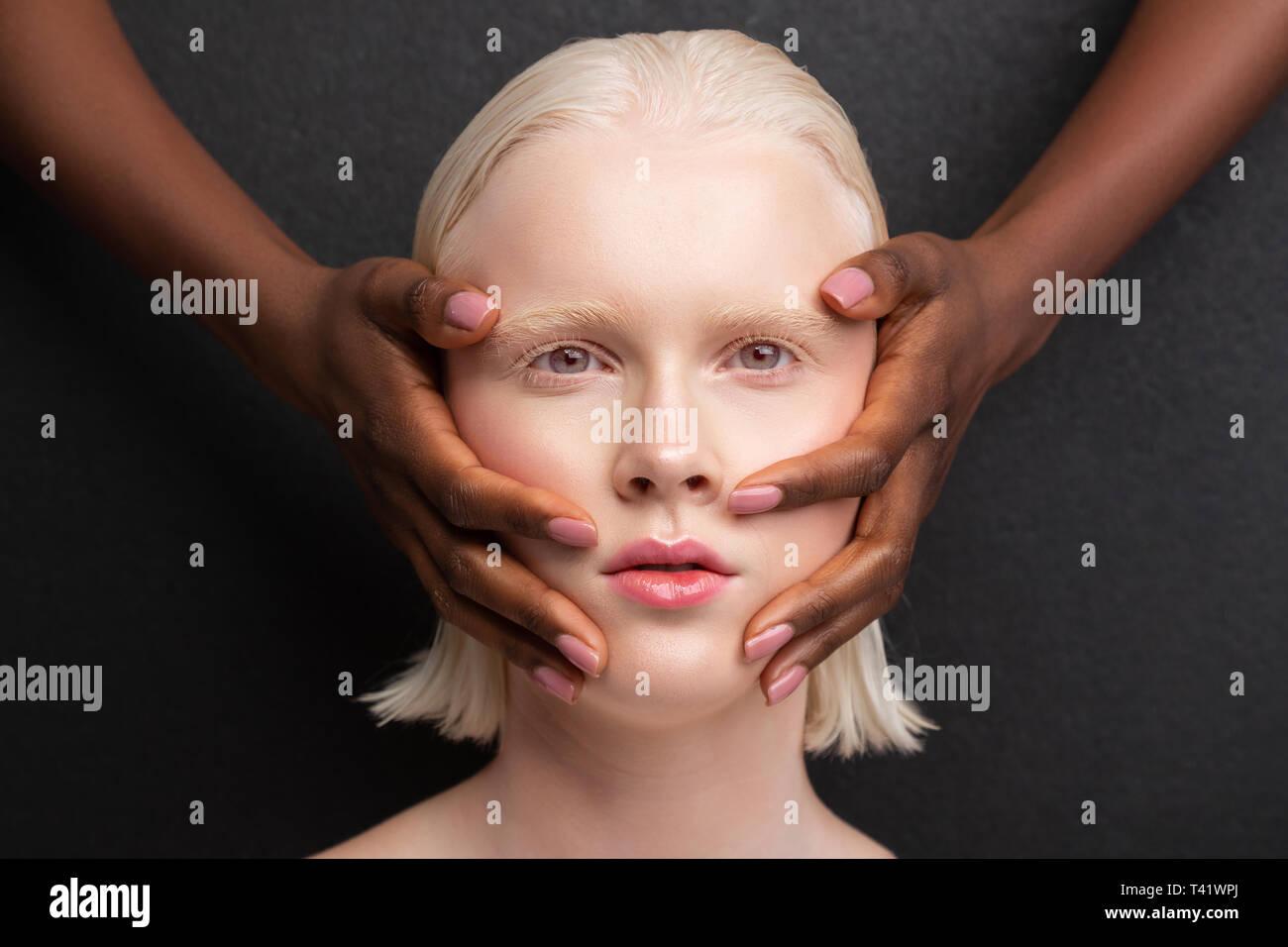 Grey-eyed woman having dark-skinned hands on face - Stock Image