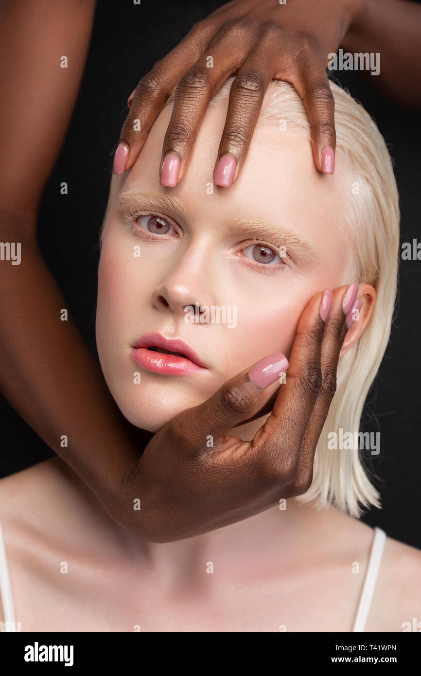 African-American woman touching face of woman with white skin - Stock Image