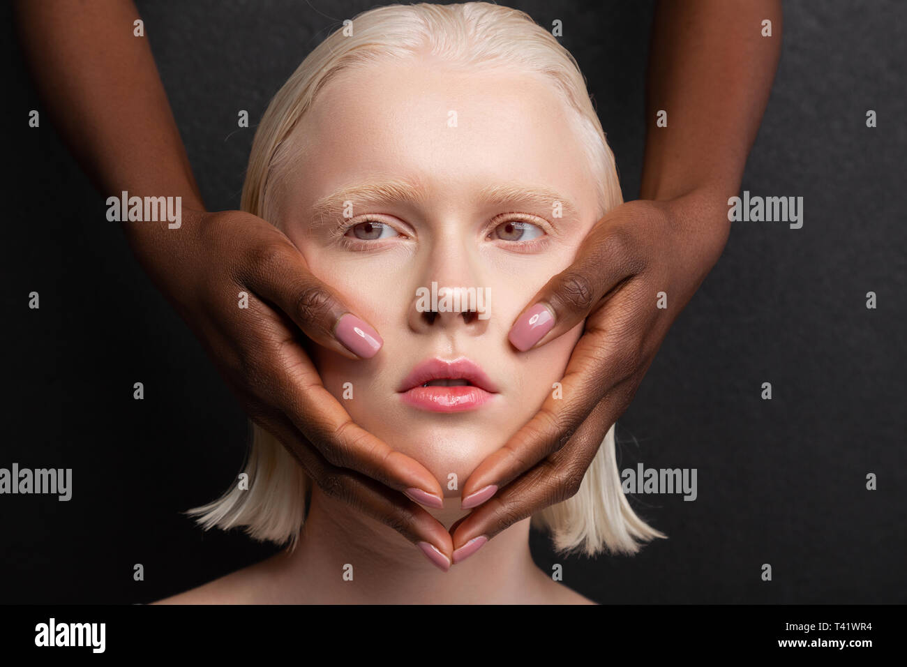 Dark-skinned hands with light pink nails touching white face - Stock Image