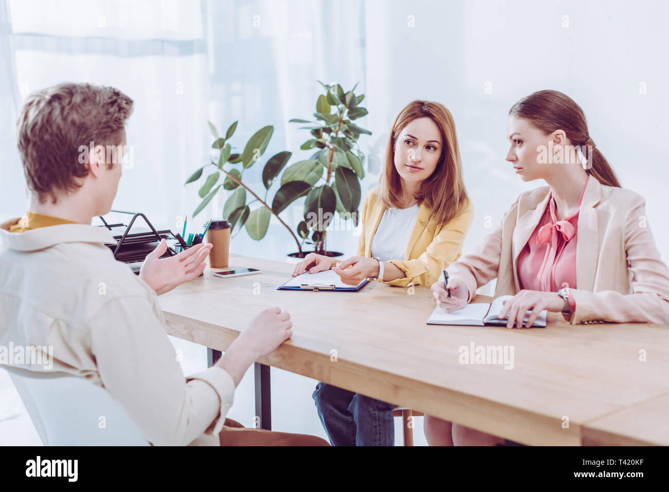 a116ac65cf84 man talking and gesturing near attractive recruiters on job interview