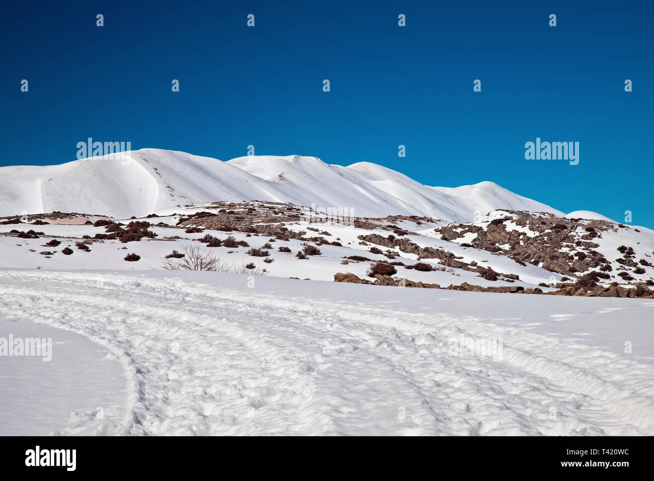 The road to Nida plateau covered with snow. In the background the highest peaks of Psiloritis mountain. Rethimno, Crete, Greece. Stock Photo