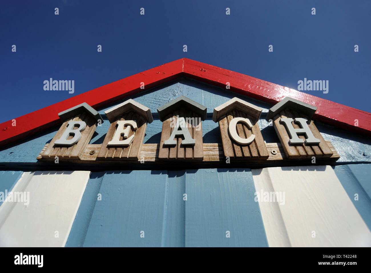 BEACH HUT WITH 'BEACH' SIGN AND BLUE SKY RE HOLIDAYS SUNSHINE WEATHER RELAXING ETC UK - Stock Image