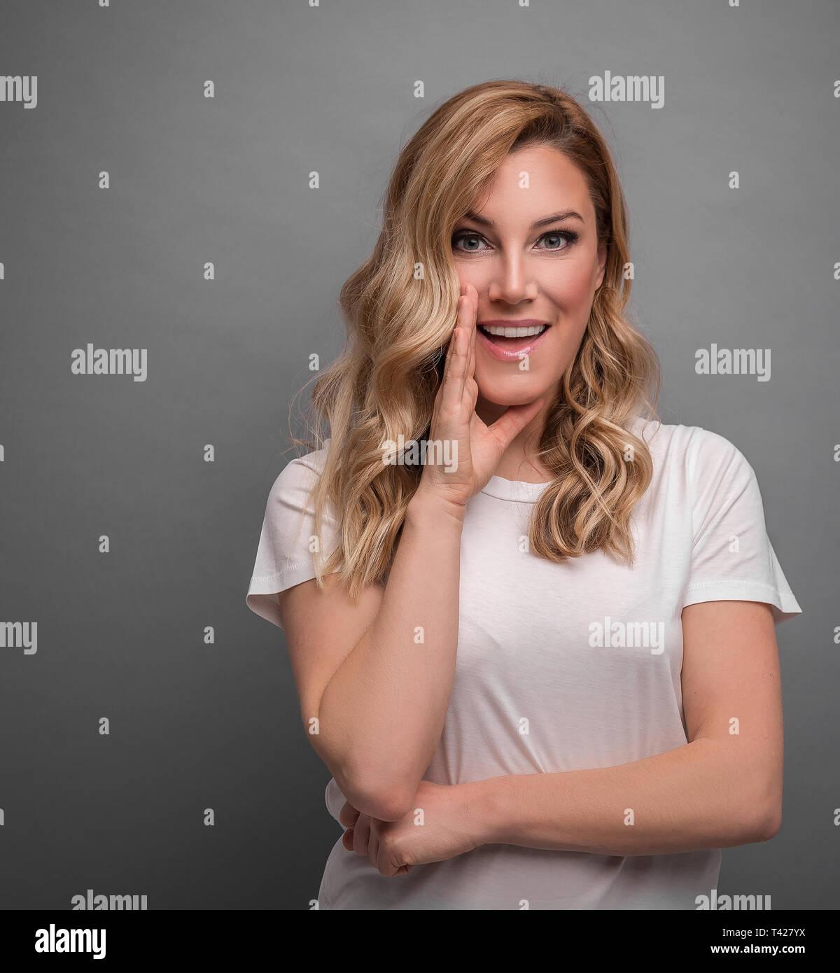 Beautiful blonde speaks about something secretly posing on gray background. - Stock Image