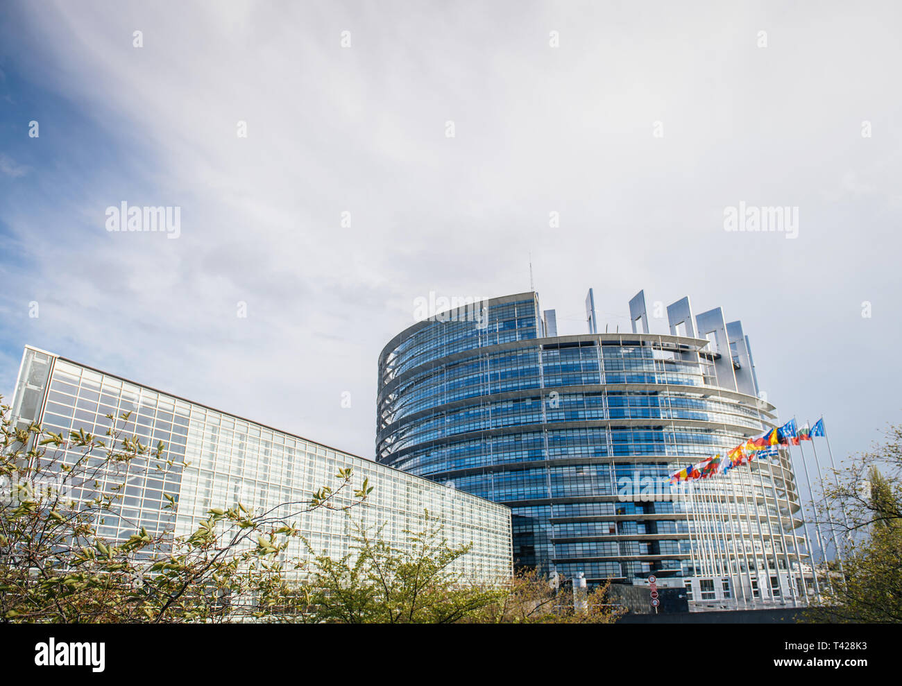 European Parliament building with all member states flags waving useful image for business articles, Brexit, Frexit, Grexit - Stock Image