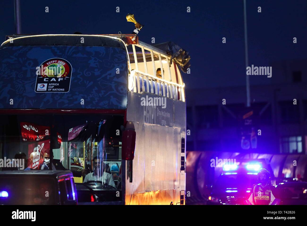 Cairo, Egypt. 12th Apr, 2019. Retired Cameroonian footballer Rigobert Song holds the Africa Cup of Nations (AFCON) trophy on top of an open top bus during a tour in the streets of Cairo ahead of the 2019 Africa Cup of Nations draw, which to take place at the Pyramids of Giza. Credit: Hassan Mohamed/dpa/Alamy Live News - Stock Image