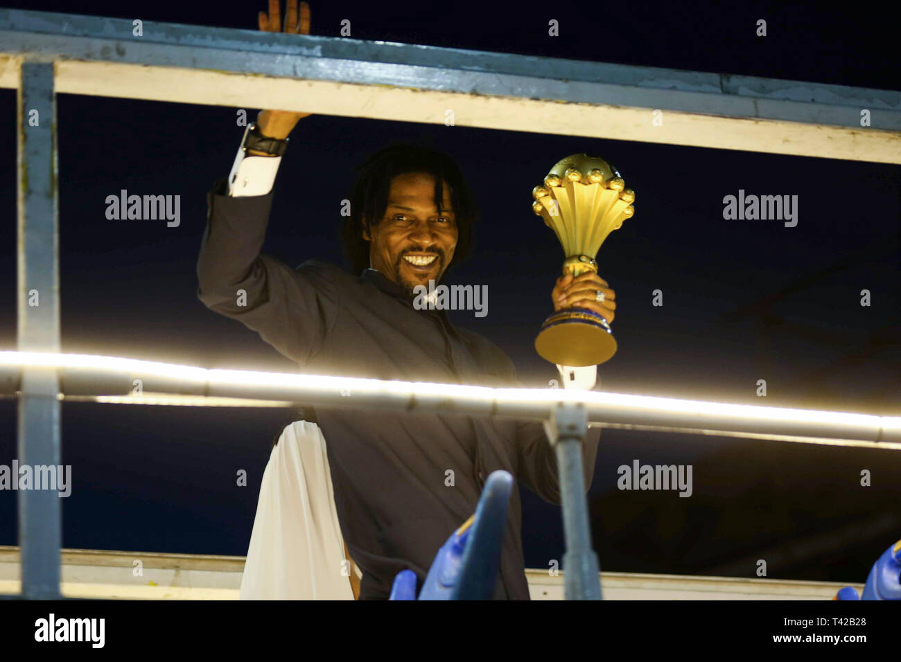 Cairo, Egypt. 12th Apr, 2019. Retired Cameroonian footballer Rigobert Song waves on top of an open top bus while holding the Africa Cup of Nations (AFCON) trophy during a tour in the streets of Cairo ahead of the 2019 Africa Cup of Nations draw, which to take place at the Pyramids of Giza. Credit: Hassan Mohamed/dpa/Alamy Live News - Stock Image