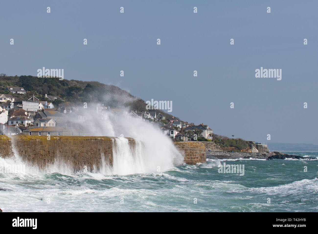 Mousehole, Cornwall, UK. 13th Apr, 2019. UK Weather. Winds of 50mph, and big waves batter the harbour wall at Mousehole this lunchtime. Despite the wind it was still sunny. Credit: Simon Maycock/Alamy Live News Stock Photo