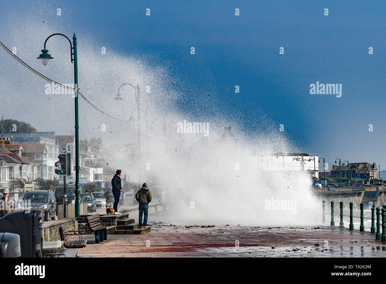 Penzance, Cornwall, UK. 13th Apr, 2019. UK Weather. Despite the sunshine it felt cold on the sea front at Penzance, as the 50mph wind pushed waves over the promenade on the seafront. Credit: Simon Maycock/Alamy Live News Stock Photo