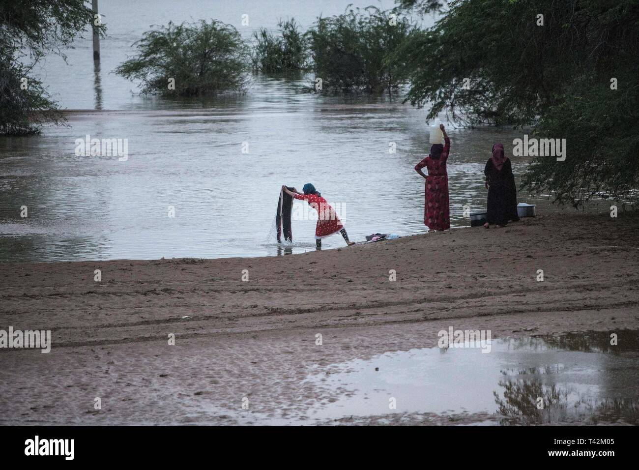 Khuzestan, Iran. 12th Apr, 2019. Women wash clothes in flood waters in Khuzestan province, Iran, on April 12, 2019. The Iranian authorities ordered this week nearly 70,000 people to flee their homes as floodwater poured into Ahvaz, capital city of the southwestern province of Khuzestan. Credit: Ahmad Halabisaz/Xinhua/Alamy Live News - Stock Image