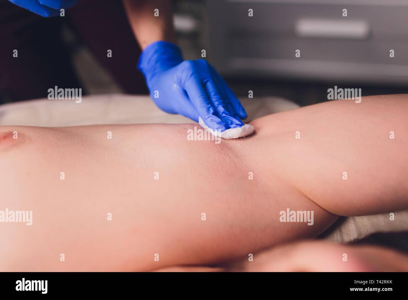 men sugaring hair removal armpit salon male. - Stock Image