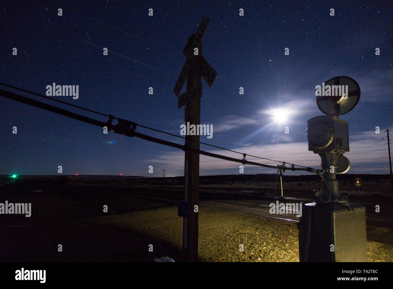 railroad crossing signal wig wag in southwestern united states delhi colorado under large night sky under moonlight along santa fe trail - Stock Image