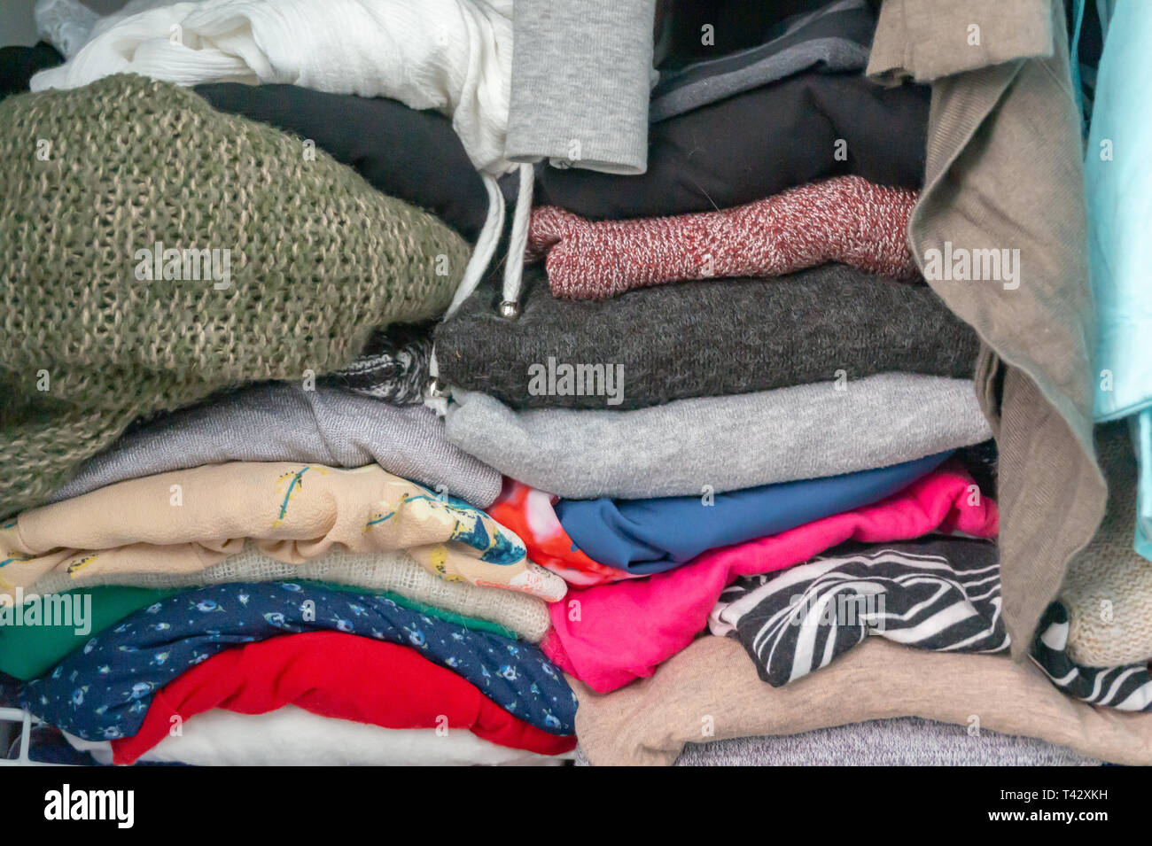 Crammed folded sweaters and garments of a woman's wardrobe in a closet. Depicting excess, the need for closet organization, tidying up, donating. - Stock Image