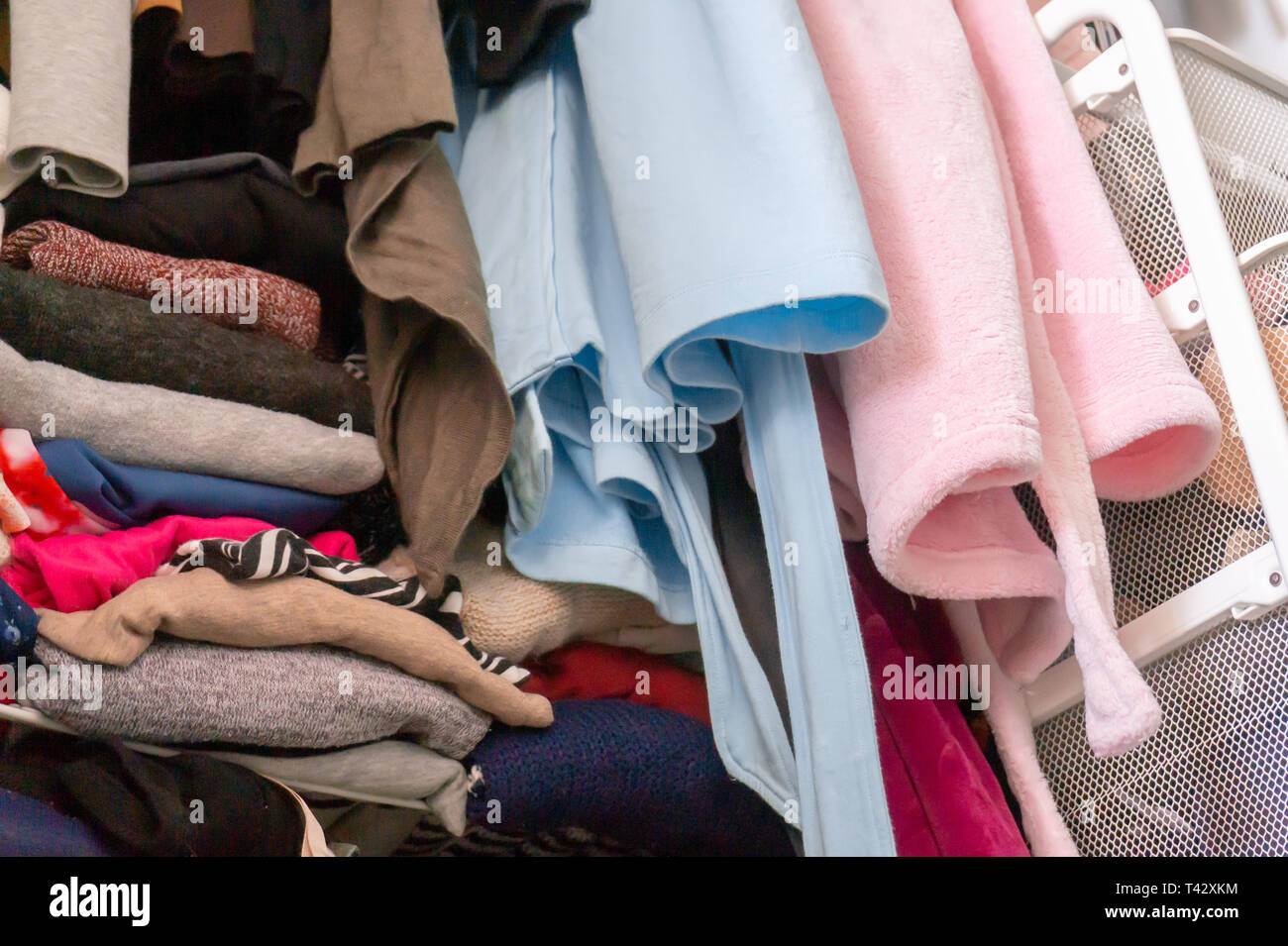 Blue and pink house robes hanging above folded, stacked and messy woman's closet, in need of closet organization. Depicting tidying up, excess. - Stock Image