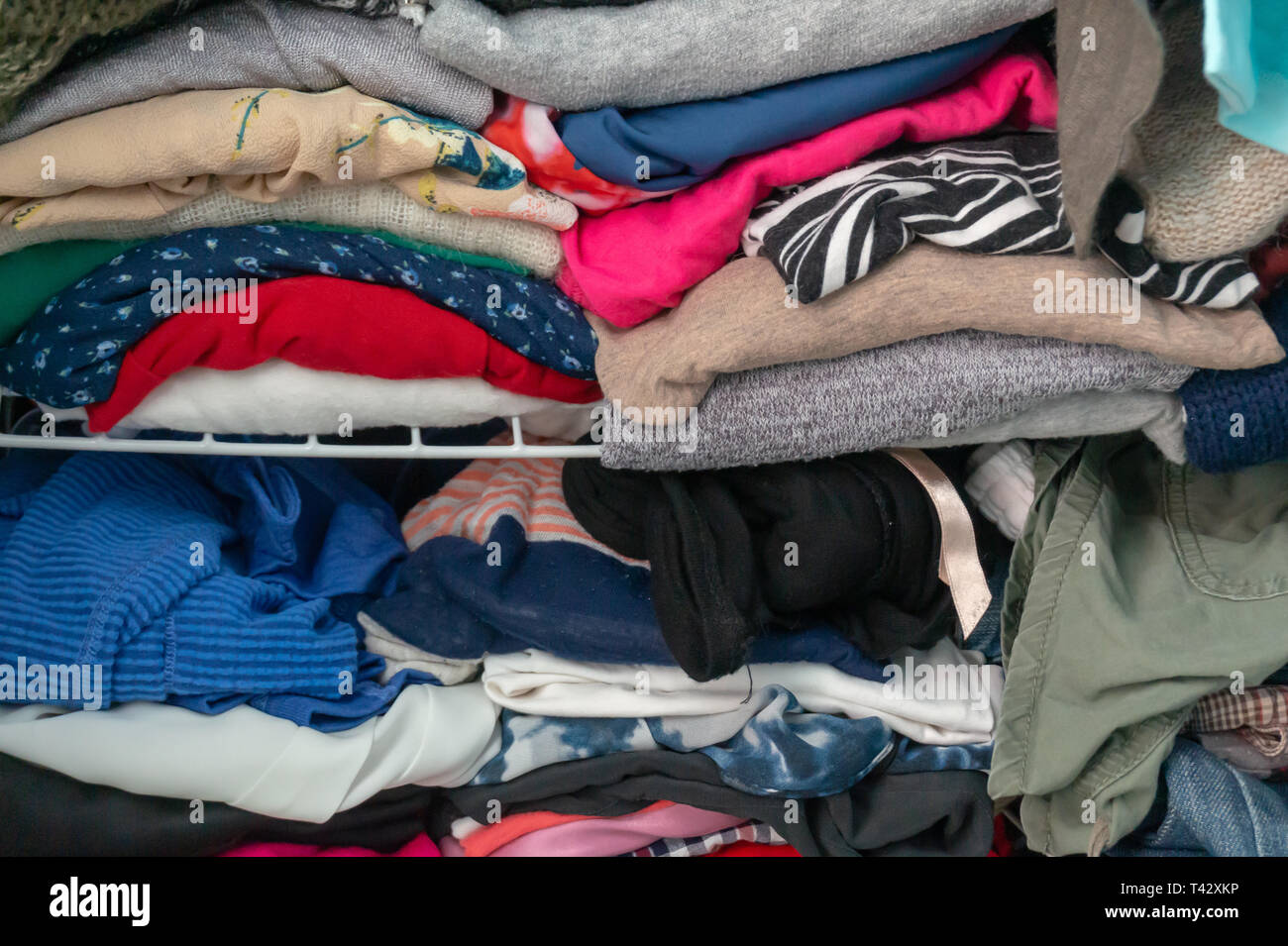 Messy folded clothes crammed in a closet on a shelf. Depicting woman's wardrobe, consumerism, cleaning up, tidying up, purging, etc. - Stock Image