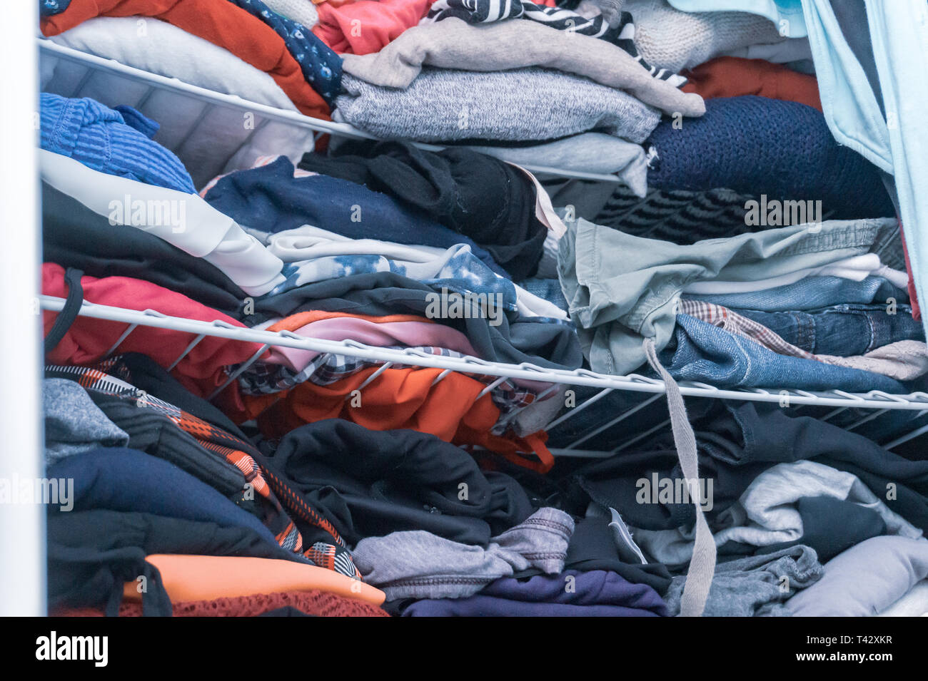 Blue and red hues of clothing in a woman's closet, folded but messy, in need of closet organization. Depicting donating clothes, tidying up. - Stock Image