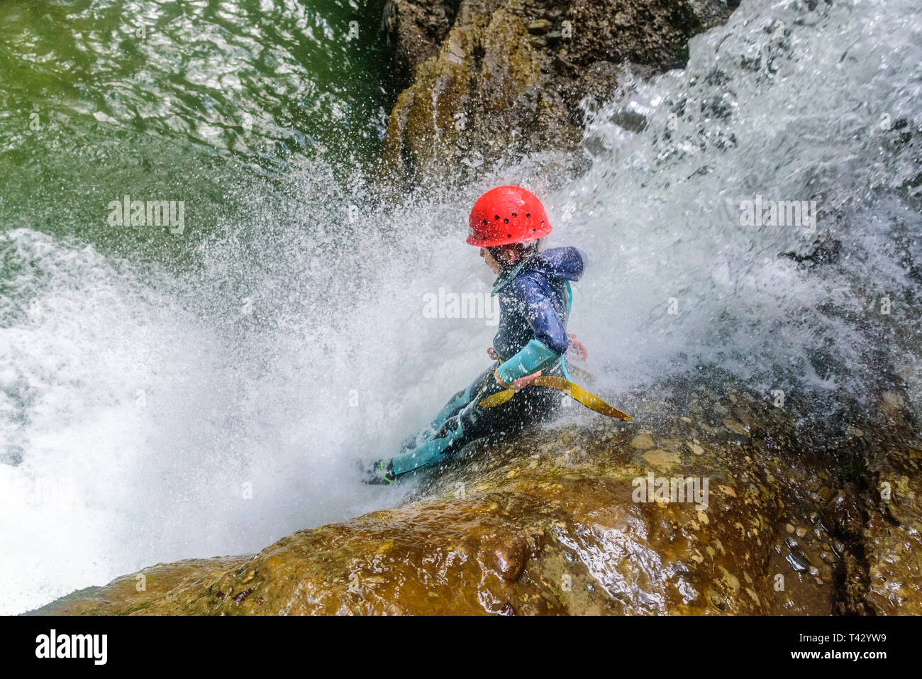 Canyoning - boy sliding on rocks in waterfall - Stock Image